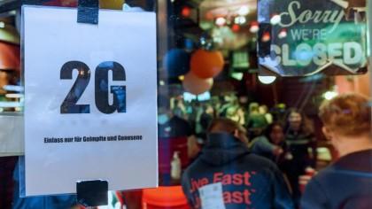 """Im Fenster einer Kneipe hängt ein Zettel mit dem Text """"2G, Einlass nur für Geimpfte und Genesene""""."""
